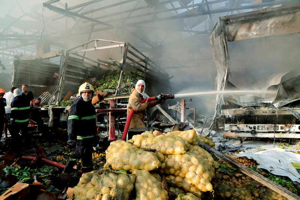 Firefighters spray water at the site of a truck bomb attack at a crowded market in Baghdad