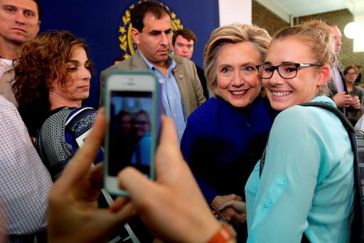 Hillary Clinton poses for a photograph with an audience member at a campaign town hall meeting in Claremont, New Hampshire