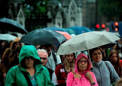 Pedestrians cover themselves from the rain with umbrellas in the City of Westminster, London Photo credit should read: Daniel Leal-Olivas/PA Wire