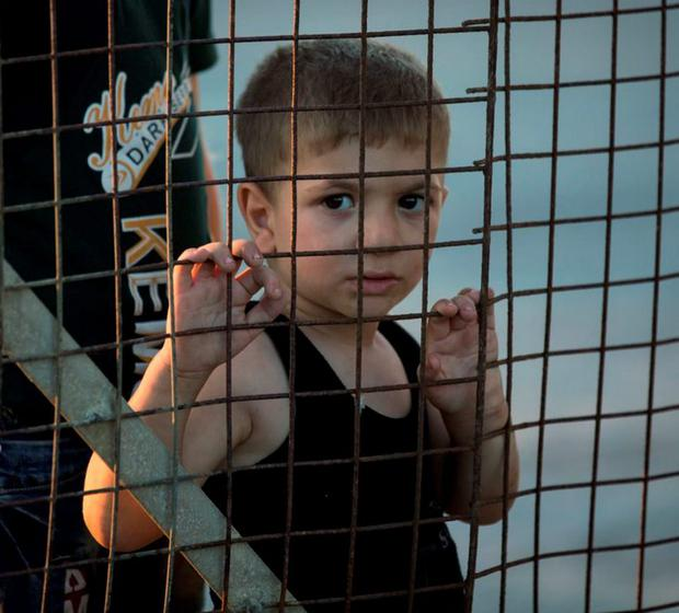 A boy looks through a fence as other migrants and refugees wait to board an Athens-bound ferry at the southeastern island of Kos in Greece this week