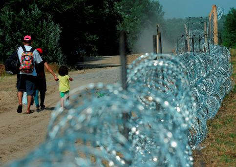 A migrant family walks by a fence that is being built on the Hungarian Serbian border at Morahalom, Hungary. Hungary's government has started to build a 175-kilometre long fence on the border in order to halt a massive flow of migrants who enter the EU via Hungary and head on to western Europe