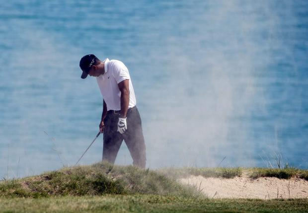 Tiger Woods covers his face after hitting from a bunker on the fourth hole during the second round