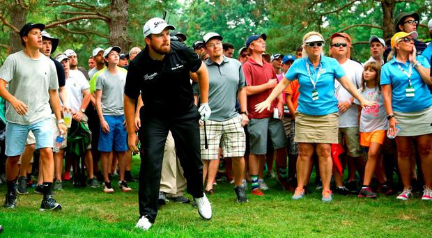 Shane Lowry watches as his approach clears the trees