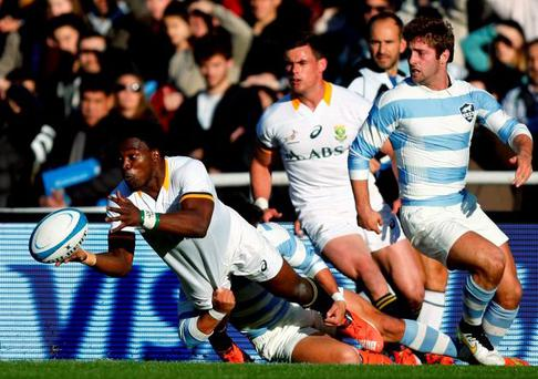 South Africa's Lwazi Mvovo passes the ball as he is tackled by Argentina's Matias Moron