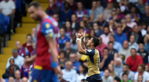 Alexis Sanchez celebrates after Crystal Palace's Damien Delaney (foreground) scores an own goal