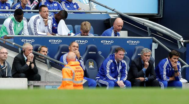 Chelsea's John Terry sits on the bench behind manager Jose Mourinho