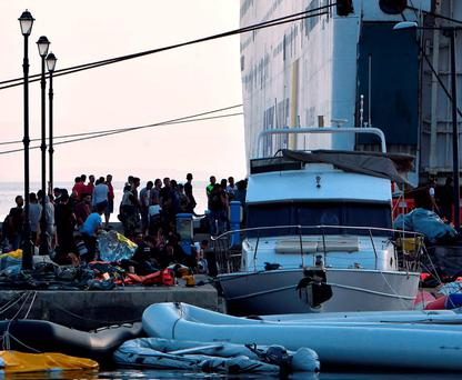 Intercepted migrants wait to board the Eleftherios Venizelos liner, which will be used to process and house them on the Greek island of Kos after chaotic scenes on-shore resulted in riot police being sent to quell rioting