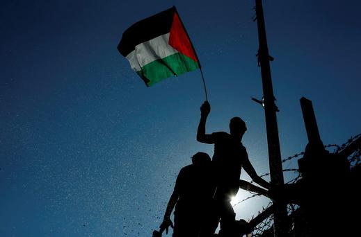 A spectator waves a Palestinian flag