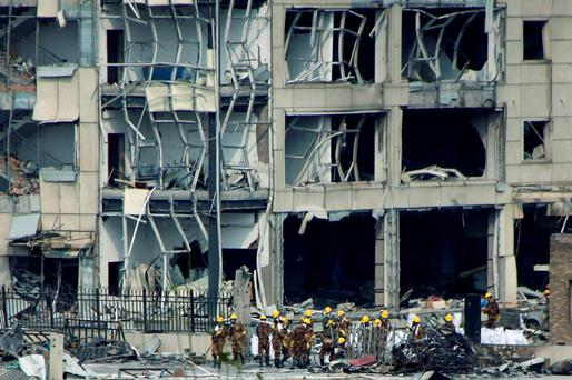 Rescue workers stand in front of a damaged building near the site of last week's explosions at Binhai new district in Tianjin