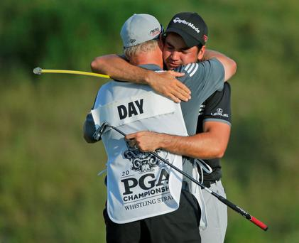 Jason Day, of Australia, hugs his caddie Colin Swatton after winning the PGA Championship golf tournament