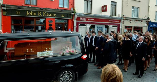 Billy, John and Conor Keane and mourners pause outside the family's famous pub as the remains of Mary Keane passes through Listowel.