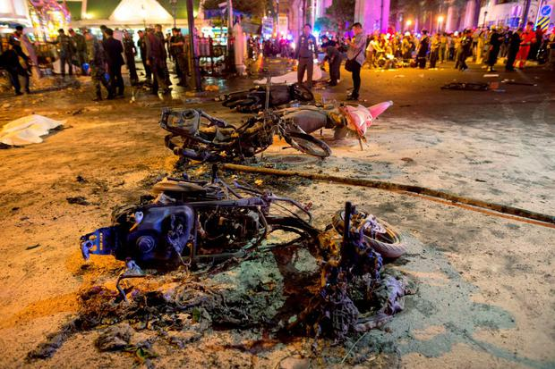 Wreckage of motorcycles are seen as security forces and emergency workers gather at the scene of a blast in central Bangkok yesterday, just outside a Hindu shrine in the centre of the Thai capital. Photo: Reuters/Athit Perawongmetha