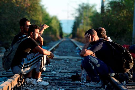 Migrants sit on railway lines near the border train station of Idomeni, northern Greece, to be allowed by the Macedonian police to cross the border from Greece to Macedonia (AP Photo/Giannis Papanikos)