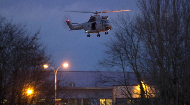 A helicopter flies over a building where the suspects of a shooting at a Paris newspaper office were holed up (AP)