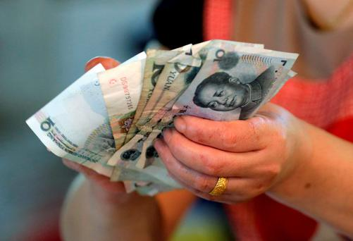 A vendor holds Chinese yuan notes at a market in Beijing