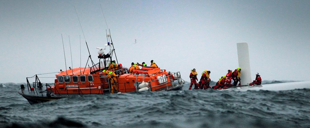 The Baltimore RNLI crew rescues the sailors from the capsized Rambler 100 – owned by George David – during the 2011 Fastnet Race in Co Cork