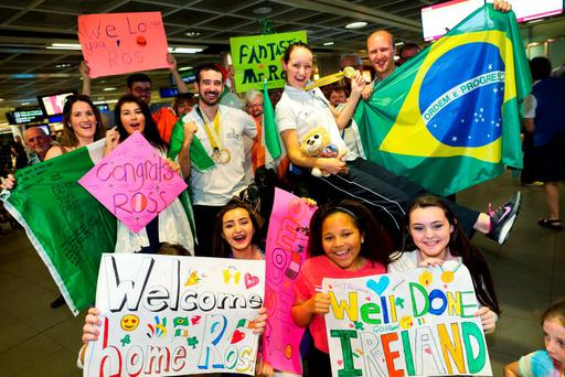 Friends and family greet gold medal-winners Alina Síle (Hotel Management) and Ros Wynne (Aircraft Maintenance) on their return to Dublin Airport from the 43rd WorldSkills Competition in Brazil. Photo: Julian Behal, Maxwells