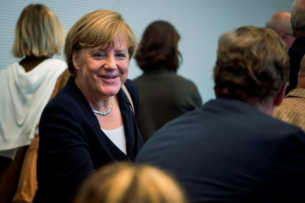 German Chancellor Angela Merkel greets colleagues as she arrives for a meeting of the parliamentarian group of the Christian Democratic Union (CDU) party at the parliament in Berlin. Photo: AFP/Getty Images