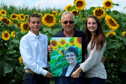 Photo: Don Jaquish pictured holding his late wife's picture after planting a field of sunflowers in her honour.