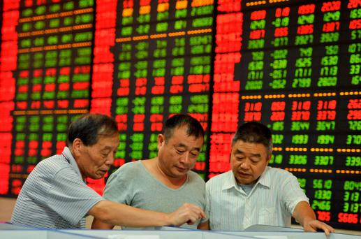 Investors look at a computer screen in front of an electronic board showing stock information at a brokerage house in Fuyang, Anhui province, China. Photo: Reuters
