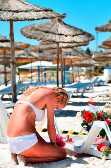 A tourist grieves at the beach where 38 people – three of them Irish – died in a terror attack in Sousse, Tunisia in June