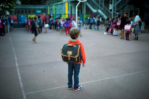 A pupil waits in the courtyard of a primary school on his first day