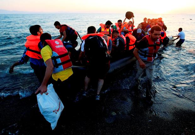 Migrants and refugees in a rubber dinghy arrive on the beach at Psalidi near Kos Town, Kos, Greece Credit: Jonathan Brady/PA Wire
