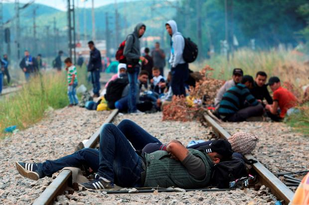 Migrants rest while waiting to pass the Greek-Macedonian border, guarded by Macedonian police near the town of Idomeni, northern Greece AFP PHOTO /SAKIS MITROLIDISSAKIS MITROLIDIS/AFP/Getty Images
