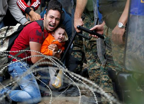 A migrant man holding a boy react as they are stuck between Macedonian riot police officers and migrants during a clash near the border train station of Idomeni, northern Greece (AP Photo/Darko Vojinovic)