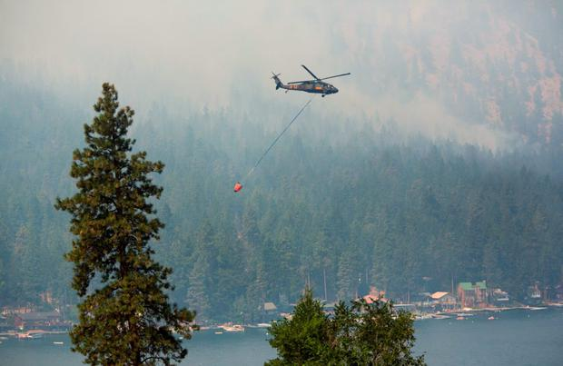 A Blackhawk military helicopter is used to make water drops during the First Creek Fire in Chelan, Washington, August 21, 2015. REUTERS/Jason Redmond