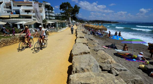 People ride their bikes along a dirt track in Marbella's Puerto Banus marina, which forms part of today's Vuelta Stage 1 team time trial route