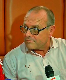 In this image made from TV, Chris Norman, the Briton who helped overpower high-speed train attacker talks to the media early Saturday Aug. 22, 2015, in Arras, France, explaining the blood stains on his shirt. (AP Photo /APTN)