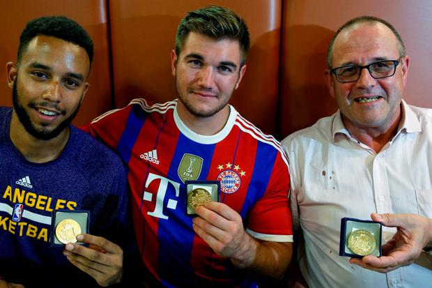 (L-R) Three men who helped to disarm an attacker on a train from Amsterdam to France, Anthony Sadler, from Pittsburg, California, Aleck Sharlatos from Roseburg, Oregon, and Chris Norman, a British man living in France, pose with medals they received for their bravery at a restaurant in Arras, France August 22, 2015. REUTERS/Pascal Rossignol