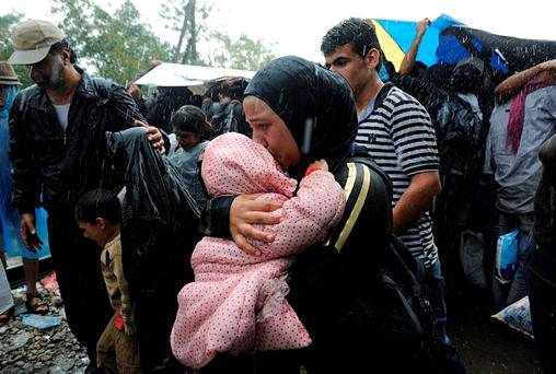 A migrant holds a child under the rain close to the border crossing between Greece and Macedonia, near the village of Idomeni, Greece, August 22, 2015. REUTERS/Alexandros Avramidis