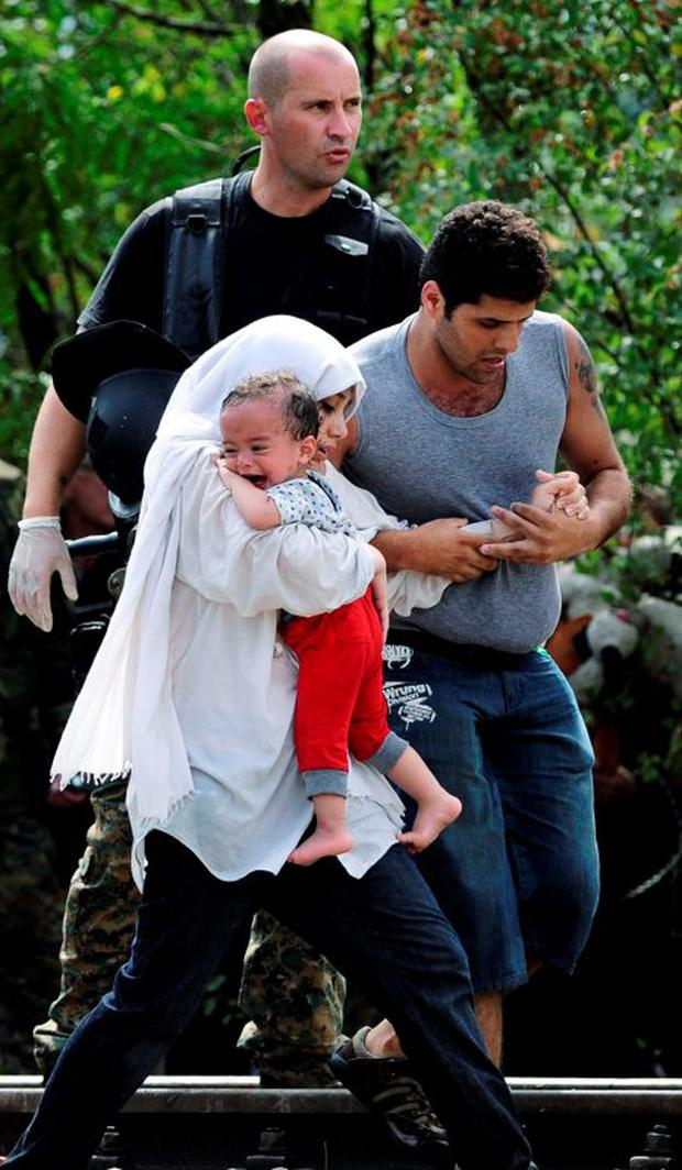 A migrant holds the hand of a woman carrying a child, as they walk towards Gevgelija, Macedonia after crossing Greece's border into Macedonia, August 22, 2015. REUTERS/Ognen Teofilovski