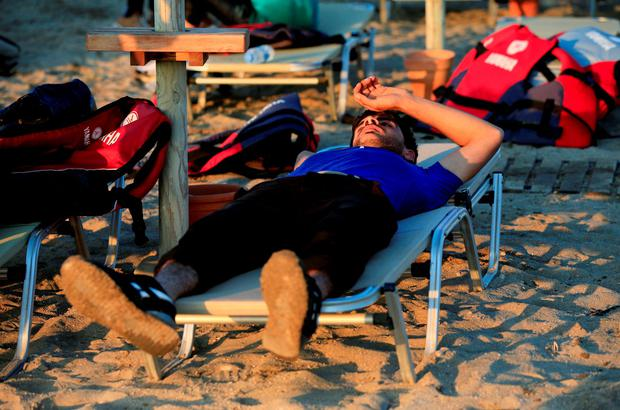 A newly arrived migrant rests on a sun lounger on the beach at Psalidi near Kos Town, Kos, Greece. Jonathan Brady/PA Wire