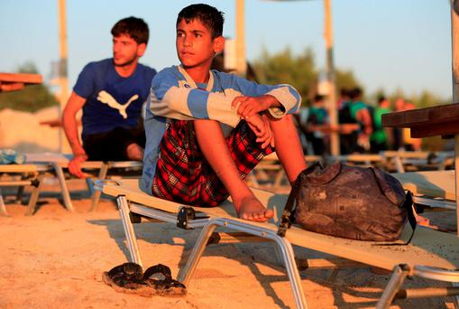 Newly arrived migrants rest on sun loungers on the beach at Psalidi near Kos Town, Kos, Greece. Jonathan Brady/PA Wire