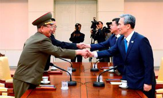 South Korean National Security Adviser Kim Kwan-jin (R), South Korean Unification Minister Hong Yong-pyo (2nd R), Secretary of the Central Committee of the Workers' Party of Korea Kim Yang Gon (2nd L), and the top military aide to the North's leader Kim Jong Un Hwang Pyong-so (L), shake hands during the inter-Korean high-level talks at the truce village of Panmunjom inside the Demilitarized Zone separating the two Koreas, South Korea, in this picture provided by the Unification Ministry and released by Yonhap on August 22, 2015. REUTERS/the Unification Ministry/Yonhap