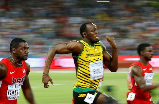 Justin Gatlin of the U.S. (L) and Usain Bolt of Jamaica (C) run to the finsih line in the men's 100 metres final during the 15th IAAF World Championships at the National Stadium in Beijing