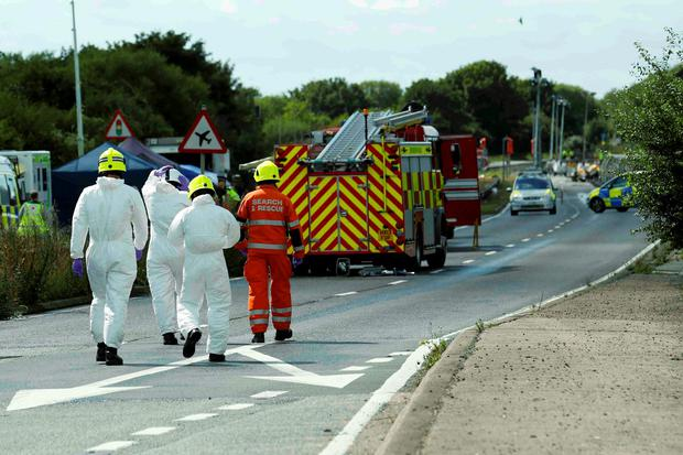 Emergency services and crash investigation officers work at the site where a Hawker Hunter fighter jet crashed onto the A27 road at Shoreham near Brighton, Britain August 23, 2015. REUTERS/Luke MacGregor