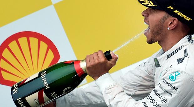 Winner Mercedes AMG Petronas F1 Team's British driver Lewis Hamilton sprays champagne as he celebrates on the podium at the Spa-Francorchamps circuit in Spa on August 23, 2015, after the Belgian Formula One Grand Prix. AFP PHOTO / JOHN THYSJOHN THYS/AFP/Getty Images