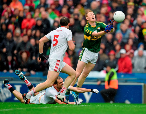 Kerry's Colm Cooper punches the ball goalwards under pressure from Tyrone players Ronan Mcnabb and Justin McMahon