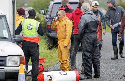 Patrick Troy (in yellow jumpsuit) and one of his rescuers after he and his son Finn were rescued from a cave in north Clare yesterday after being stuck for 28 hours Picture Credit Press 22