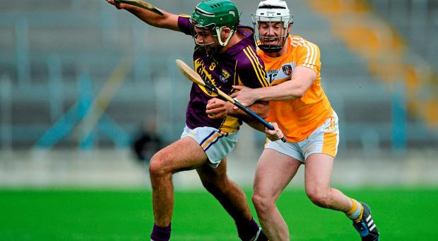Wexford's Conor Devitt attempts to drive past Michael Dudley