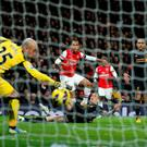 Arsenal's English striker Theo Walcott scores a goal beating Liverpool's Spanish goalkeeper Pepe Reina to take the score to 2-2 during the English Premier League football match between Arsenal and Liverpool at The Emirates Stadium, January 30, 2013
