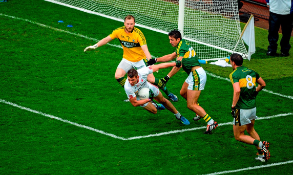 Tyrone's Pádraig McNulty falls to the ground under pressure from Aidan O'Mahony – McNulty was booked by referee Maurice Deegan