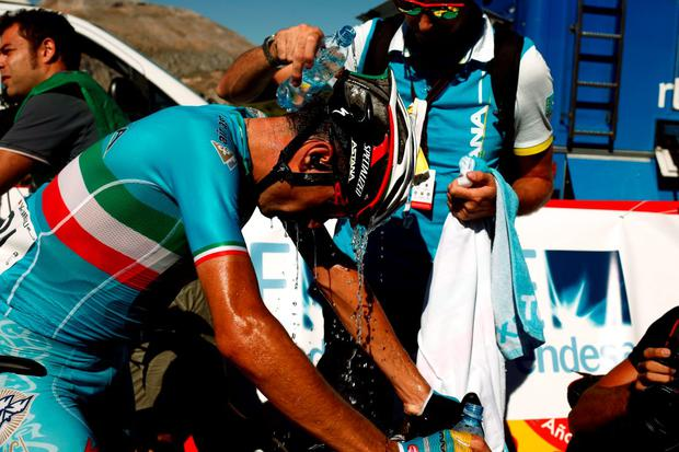 Astana Pro Team rider Vincenzo Nibali of Italy is cooled with water by a team member after finishing the 158.7 km (98.6 miles) 2nd stage of the Vuelta Tour of Spain cycling race from Alhaurin de la Torre to Caminito del Rey, in Ardales, southern Spain, August 23, 2015. REUTERS/Jon Nazca