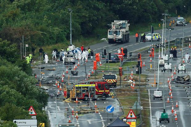 A crane arrives on site as emergency services and crash investigation officers continue to work at the site where a Hawker Hunter fighter jet crashed onto the A27 road at Shoreham near Brighton, Britain August 24, 2015. Reuters/Luke MacGregor