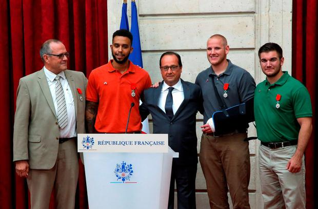 From the left, British businessman Chris Norman, Anthony Sadler, a senior at Sacramento University in California, French President Francois Hollande, U.S. Airman Spencer Stone, and Alek Skarlatos a U.S. National Guardsman from Roseburg, Oregon pose at the Elysee Palace, Monday Aug.24, 2015 in Paris, France. (AP Photo/Michel Euler, Pool)