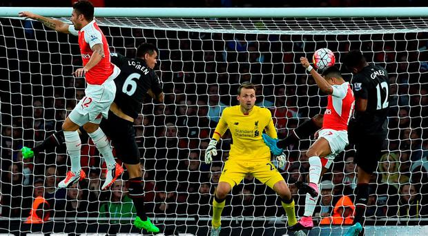 Arsenal's Chilean striker Alexis Sanchez (2R) heads the ball goalward by Liverpool's Belgian goalkeeper Simon Mignolet (C) during the English Premier League football match between Arsenal and Liverpool at the Emirates stadium, north London on August 24, 2015. AFP PHOTO / BEN STANSALL